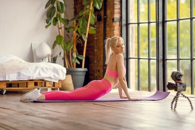 Junge sportlich fit schlanke frau trainer üben video online-training yogalehrer
