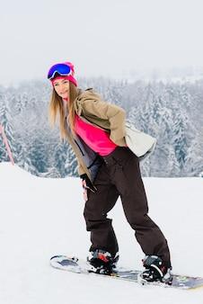 Junge sportlich lächelnde frau im winter mit snowboard, brille