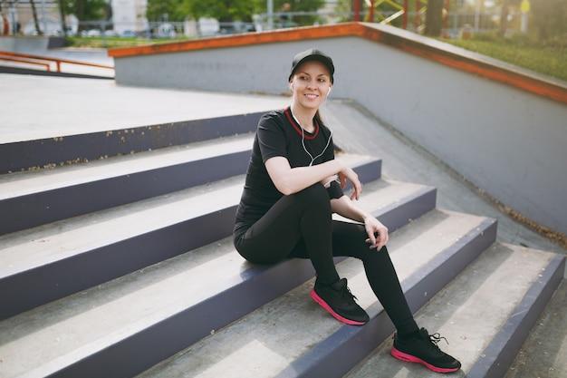 Junge sportlich lächelnde frau in schwarzer uniform und mütze mit kopfhörern, die musik hören, sich vor oder nach dem laufen ausruhen und sitzen, auf treppen im stadtpark im freien trainieren training