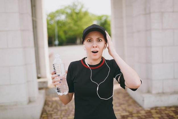 Junge sportlich schockierte schöne brünette frau in schwarzer uniform und mütze mit kopfhörern, die eine flasche mit wasser halten, musik hören, die hände im stadtpark im freien ausbreitet