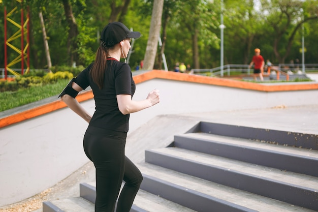 Junge sportlich schöne brünette frau in schwarzer uniform, mütze mit kopfhörern sportübungen, training und laufen, treppensteigen im stadtpark im freien in