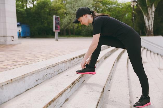 Junge sportlich schöne brünette frau in schwarzer uniform und mütze, die sportübungen macht, aufwärmen vor dem laufen, schnürsenkel auf treppen im stadtpark im freien binden