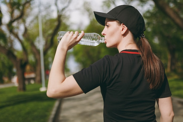 Junge sportlich schöne brünette frau in schwarzer uniform und mütze mit flasche, trinkwasser während des trainings, bevor sie im stadtpark im freien stehend läuft