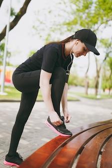 Junge sportlich schöne brünette frau in schwarzer uniform und mütze mit kopfhörern, die musik hören, schnürsenkel vor dem laufen binden, auf der bank im stadtpark im freien trainieren