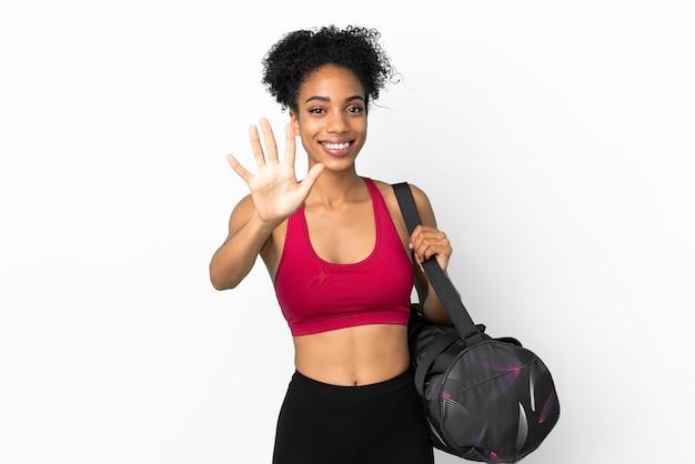 Junge sportliche afroamerikanerin mit sporttasche isoliert auf blauem hintergrund, die fünf mit den fingern zählt
