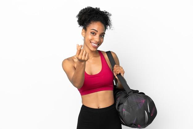 Junge sportliche afroamerikanische frau mit sporttasche auf blauem hintergrund isoliert, die geldgeste macht