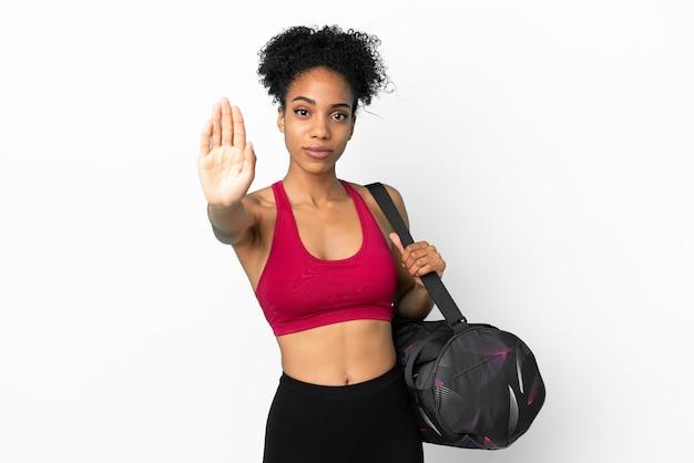 Junge sportliche afroamerikanische frau mit sporttasche auf blauem hintergrund isoliert, die stop-geste macht