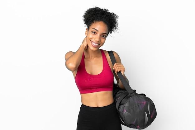 Junge sportliche afroamerikanische frau mit sporttasche auf blauem hintergrund lachend