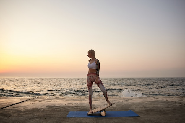 Junge sportliche blonde frau mit körper in guter körperlicher verfassung, die über meerblick aufwirft, sportliche kleidung trägt und auf balancebrett während sonnenaufgang steht