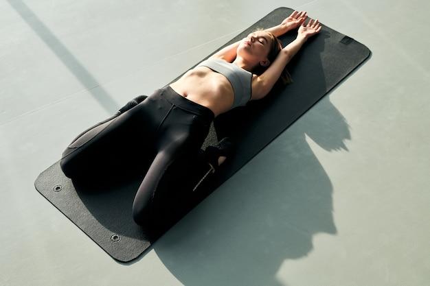 Junge sportliche entspannte frau in aktivkleidung, die auf schwarzer matte mit gebeugten knien und gestreckten armen während des trainings liegt