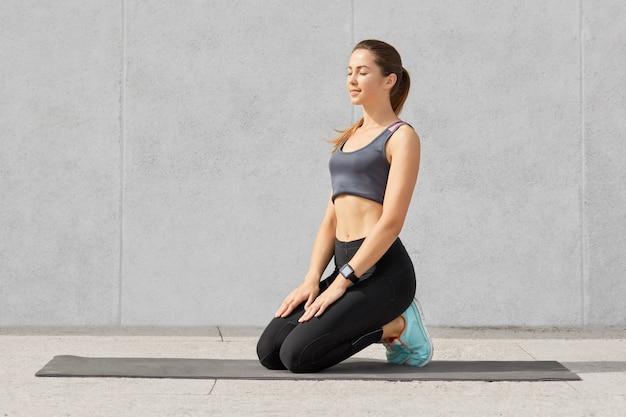 Junge sportliche europäische fitnessfrau sitzt auf matte, versucht nach dem dehnen oder üben von yoga eine pause einzulegen, hält die augen geschlossen
