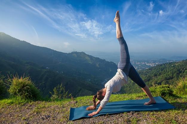 Junge sportliche fit frau, die yoga draußen tut