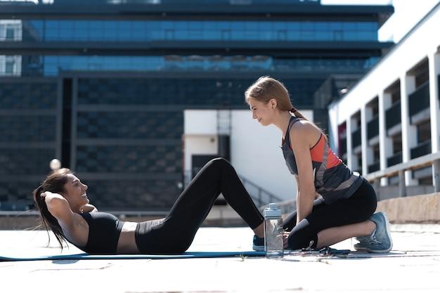 Junge sportliche, fitte, aktive freundinnen, die sit-ups im freien in der stadt machen.