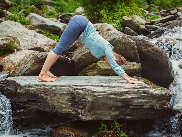 Junge sportliche fitte frau, die yoga draußen am tropischen wasserfall tut