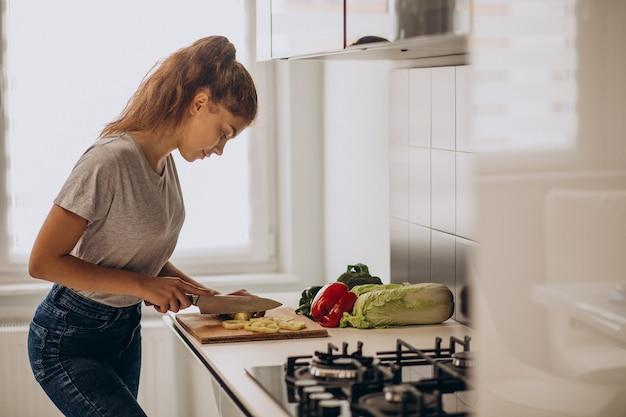 Junge sportliche frau, die an der küche kocht