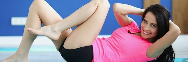 Junge sportliche frau, die auf bauchmuskeln trainiert