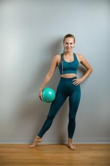 Junge sportliche frau, die auf fitball, fitnessmotivation, grauer hintergrund sitzt. sportbanner, kopierraum, schöner körper.