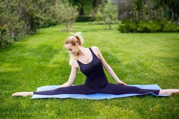 Junge sportliche frau, die auf gras im park, gymnastische spalten sitzt