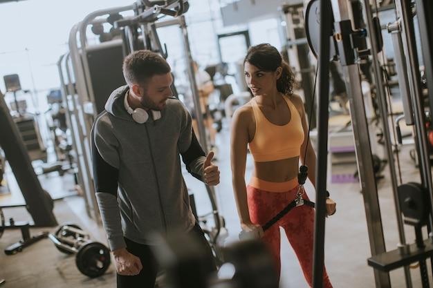 Junge sportliche frau, die auf pull-down-maschine in der turnhalle mit persönlichem trainer ausarbeitet