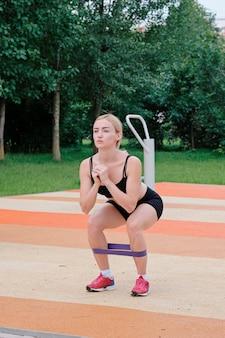 Junge sportliche frau, die draußen sport, eignungsübungen tut.
