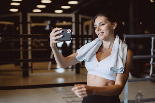 Junge sportliche frau, die ein selfie mit handy für soziale netzwerke an der turnhalle nimmt.