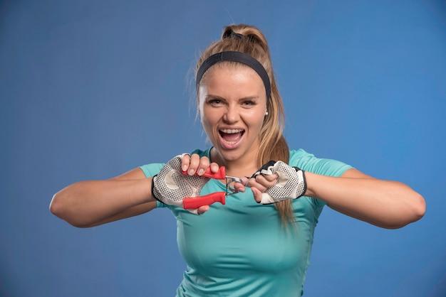 Junge sportliche frau, die eine hand hält, die kaugummi streckt und stark aussieht.