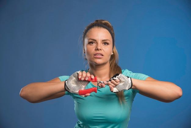 Junge sportliche frau, die einen handstretchgummi hält.