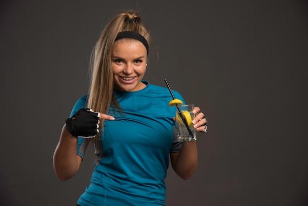 Junge sportliche frau, die energiegetränk hat und darauf zeigt.
