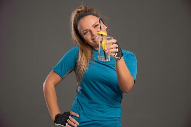 Junge sportliche frau, die energiegetränk hat und positiv aussieht.