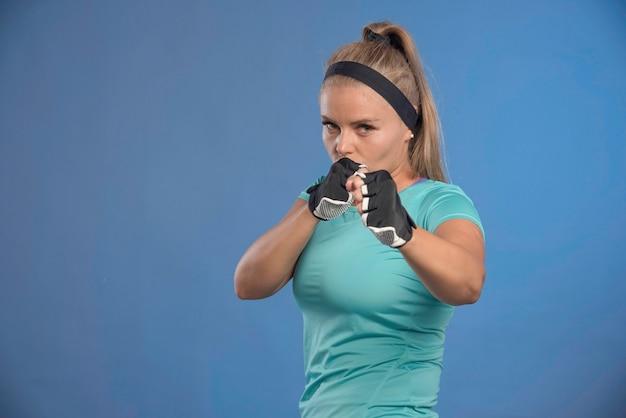 Junge sportliche frau, die fäuste und boxen hält.