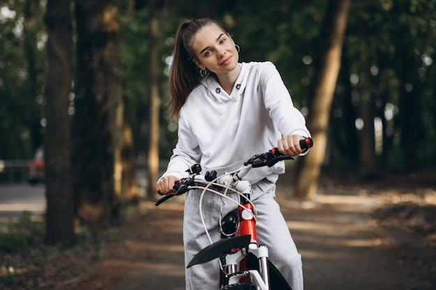 Junge sportliche frau, die fahrrad im park reitet
