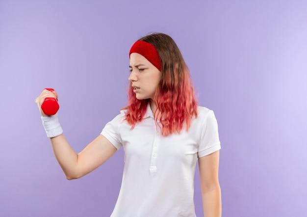 Junge sportliche frau, die hantel hält, die übungen macht, die über lila wand stehen