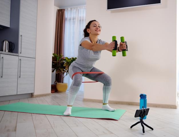 Junge sportliche frau, die hantelkniebeugen mit elastischem fitnessband durchführt, während workout-tutorials beobachtet. training zu hause