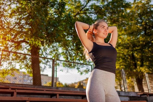 Junge sportliche frau, die ihr haar im sommer auf dem sportplatz zu einem pferdeschwanz bindet. vorbereitung für das outdoor-workout