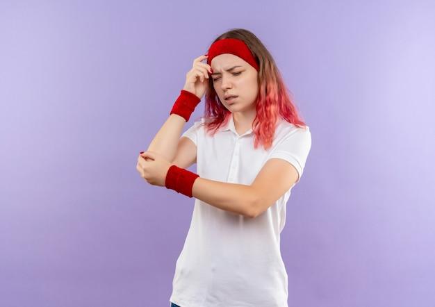 Junge sportliche frau, die ihren ellbogen berührt, der schmerz fühlt, der über lila wand steht