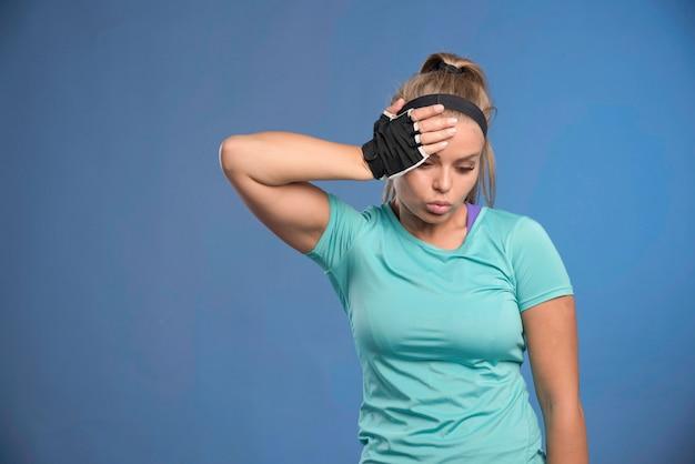 Junge sportliche frau, die ihren kopf mit einer hand hält.