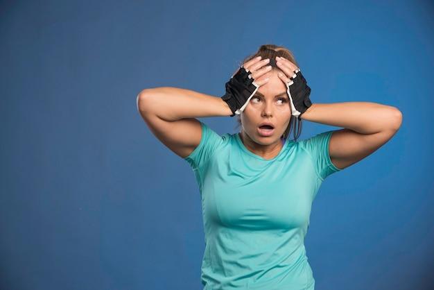 Junge sportliche frau, die ihren kopf mit zwei händen hält.