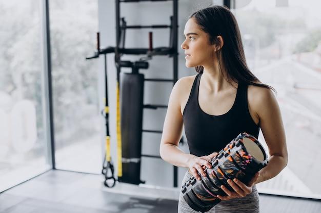 Junge sportliche frau, die im fitnessstudio trainiert