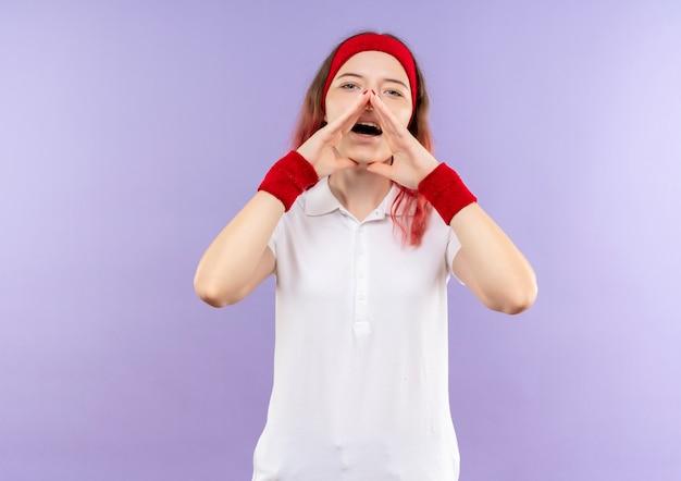 Junge sportliche frau, die jemanden mit armen nahe dem mund schreit oder ruft, der über lila wand steht