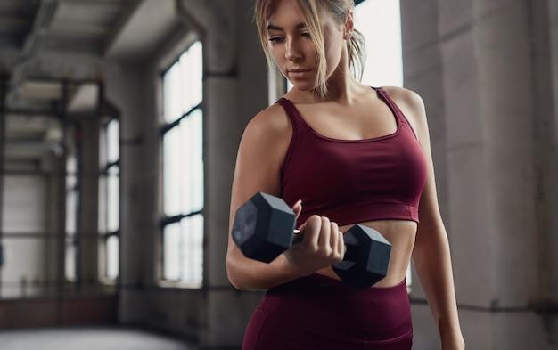 Junge sportliche frau, die mit hantel trainiert, während bizepsmuskeln während des fitness-trainings im fitnessstudio trainieren