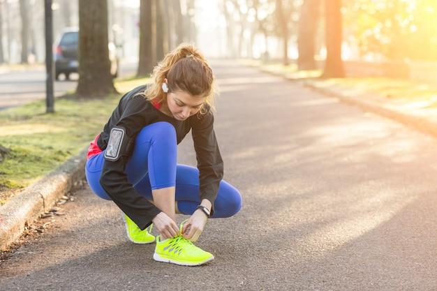 Junge sportliche frau, die oben ihre schuhe bevor dem laufen tut.