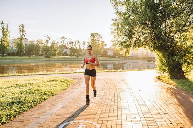 Junge sportliche frau, die sportkleidung trägt, die morgens im öffentlichen park läuft