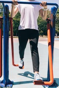 Junge sportliche frau, die übungen für beine auf dem spielplatz im sommer tut