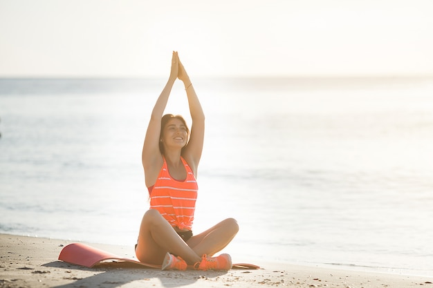 Junge sportliche frau, die yogaübungen am strand tut