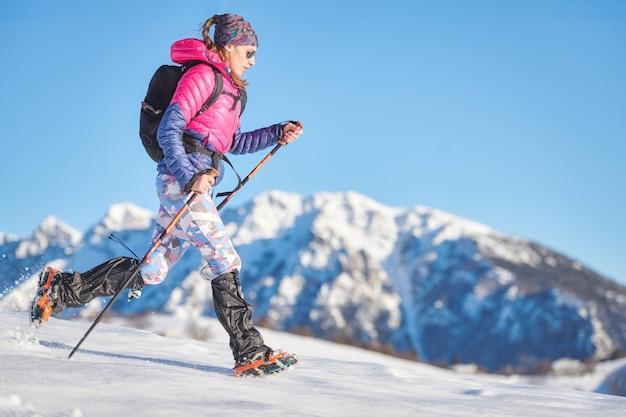 Junge sportliche frau im schnee mit steigeisen und gamaschen