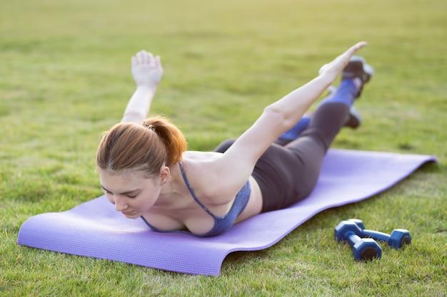 Junge sportliche frau im sportkleidungstraining im feld bei sonnenaufgang. mädchen, das in der plankenposition auf gras in einem stadtpark steht.