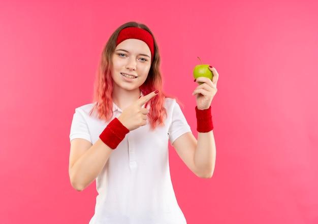 Junge sportliche frau im stirnband, die grünen apfel hält, der mit dem finger zeigt, der zuversichtlich über rosa wand steht