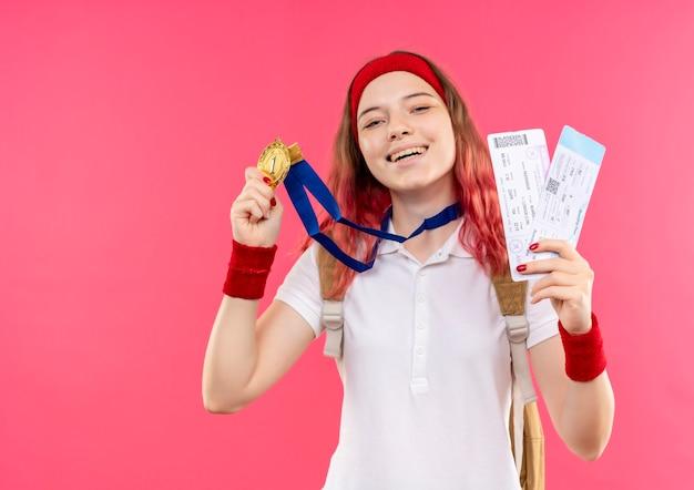 Junge sportliche frau im stirnband, die ihre goldmedaille hält, die zwei flugtickets lächelnd mit glücklichem gesicht über rosa wand steht