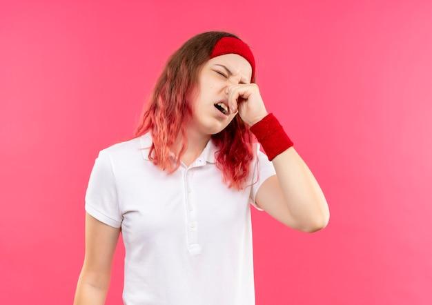 Junge sportliche frau im stirnband, die ihre nase mit den fingern schließt, die unter gestank leiden, der über rosa wand steht