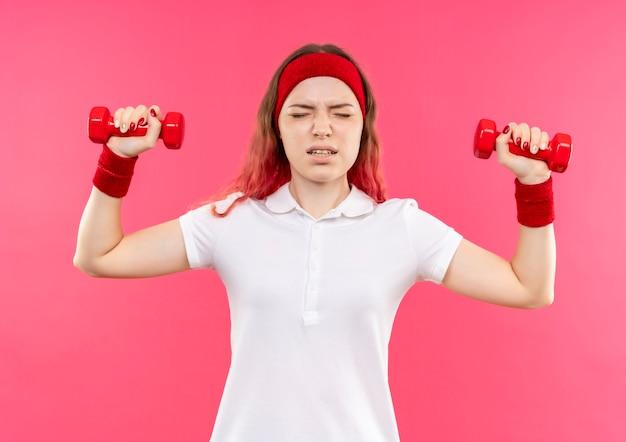 Junge sportliche frau im stirnband, die übungen mit hanteln macht, die müde und erschöpft über rosa wand stehen